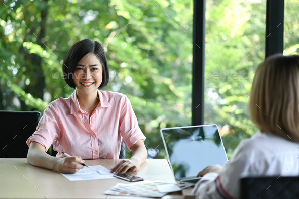 New young business woman sitting in an office, looking and smiling. - Stock Photo - Images