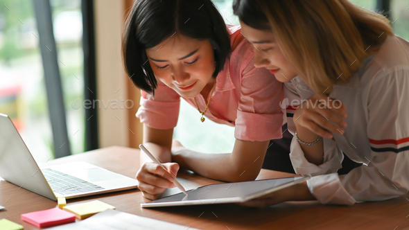 Asian female graphic designer working together at the office They use laptop and tablet. - Stock Photo - Images