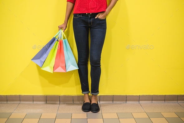 Woman legs with colourful shopping bags in a colourful wall - Stock Photo - Images