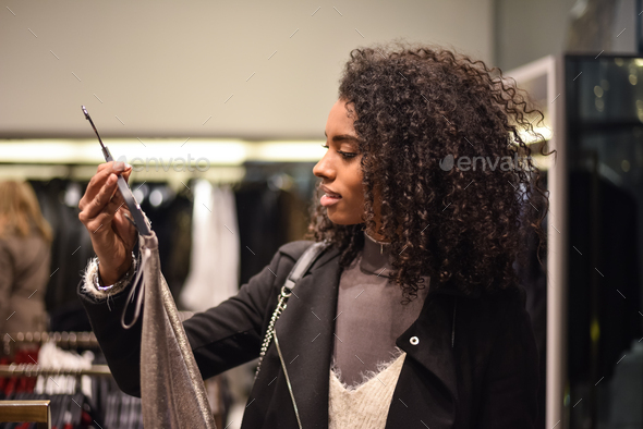 Black young woman doing shopping in a store - Stock Photo - Images