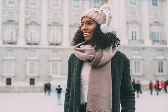 Young black woman listening to music and dancing on the mobile phone near the royal palace in winter - Stock Photo - Images