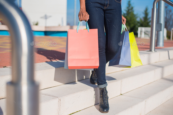 Woman walking out from a shopping mall with colourful shopping bags - Stock Photo - Images