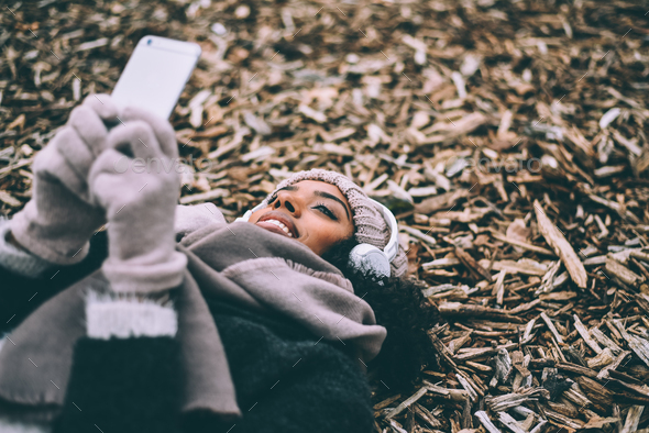 woman on the mobile phone lying on peaces of wood near the royal palace in Madrid during winter - Stock Photo - Images