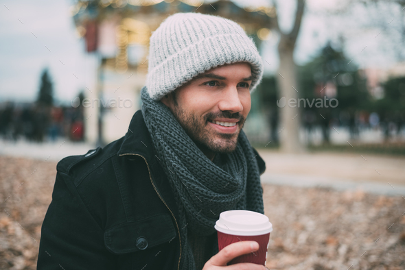 Young blonde man drinking coffee near the royal palace in winter - Stock Photo - Images