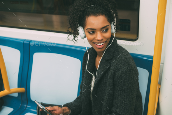 Happy young black woman sitting inside the underground listening to music - Stock Photo - Images