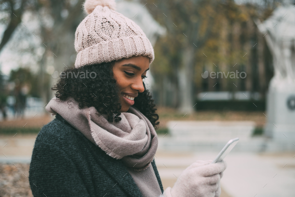 Young black woman on the mobile phone near the royal palace in winter - Stock Photo - Images