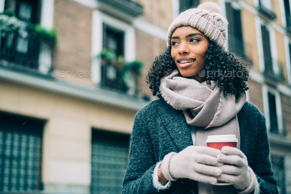 Young black woman drinking coffee wandering in the streets of Madrid on winter - Stock Photo - Images