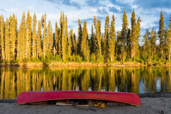 Red canoe on shore of Nisutlin River Yukon Canada - Stock Photo - Images