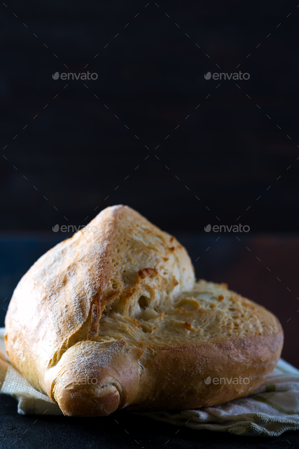 Homemade french bread with a napkin on a dark background, close-up - Stock Photo - Images