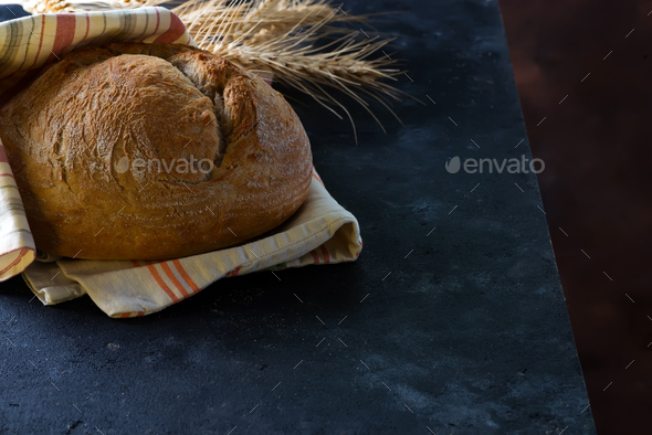 Round freshly baked rustic rye round bread with wheat ears and napkin on a dark background, copy - Stock Photo - Images