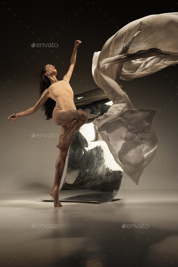 Young and stylish modern ballet dancer on brown background - Stock Photo - Images