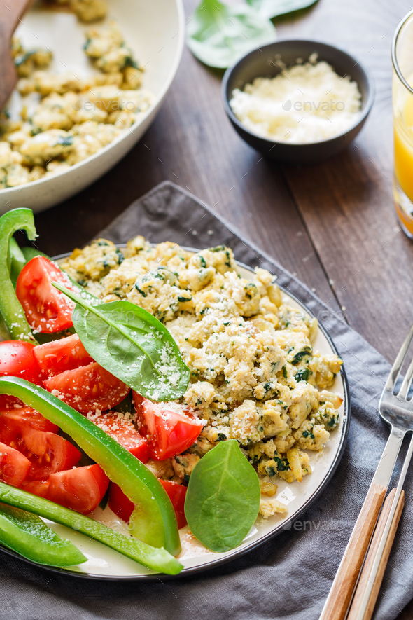 Breakfast table with a portion of spinach scrambled eggs - Stock Photo - Images