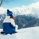 A girl with a ski mask in a blue suit sits on a snowboard in the - PhotoDune Item for Sale