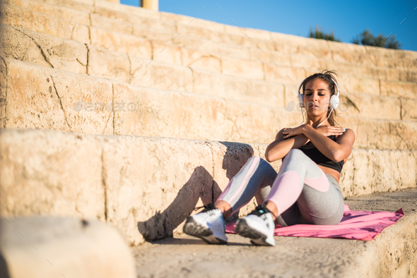 sportswoman outdoor in a stairs doing exercise listening music - Stock Photo - Images