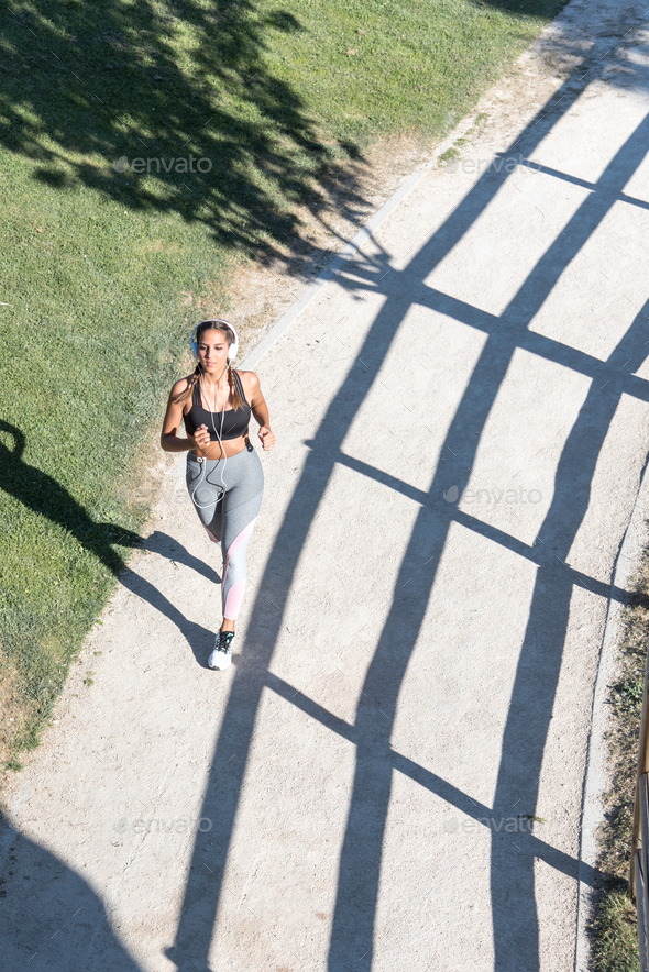 young Woman running jogging in a park outdoors listening music - Stock Photo - Images