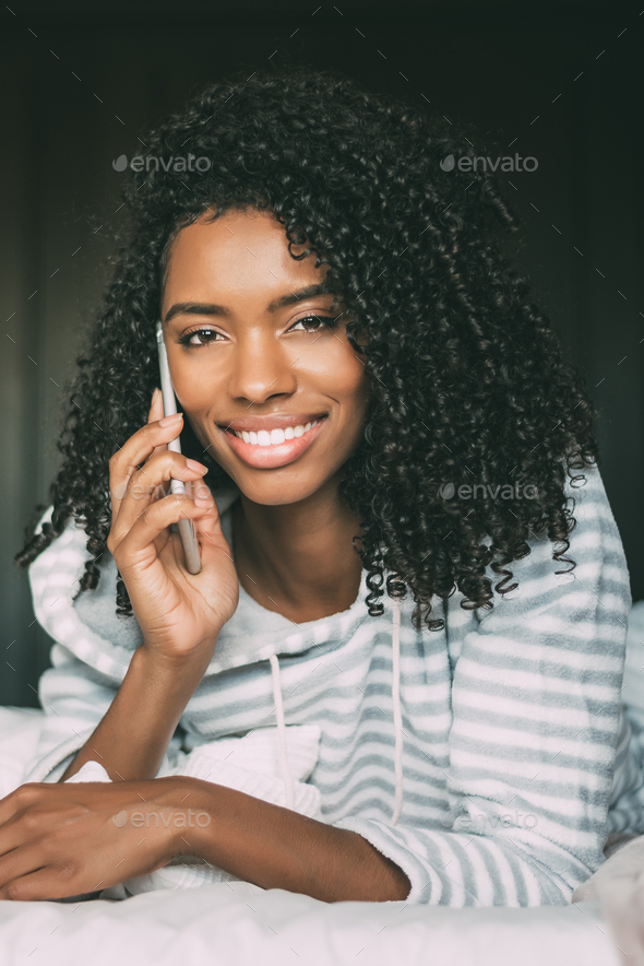 close up of a pretty black woman with curly hair with smartphone on bed looking at the camera - Stock Photo - Images