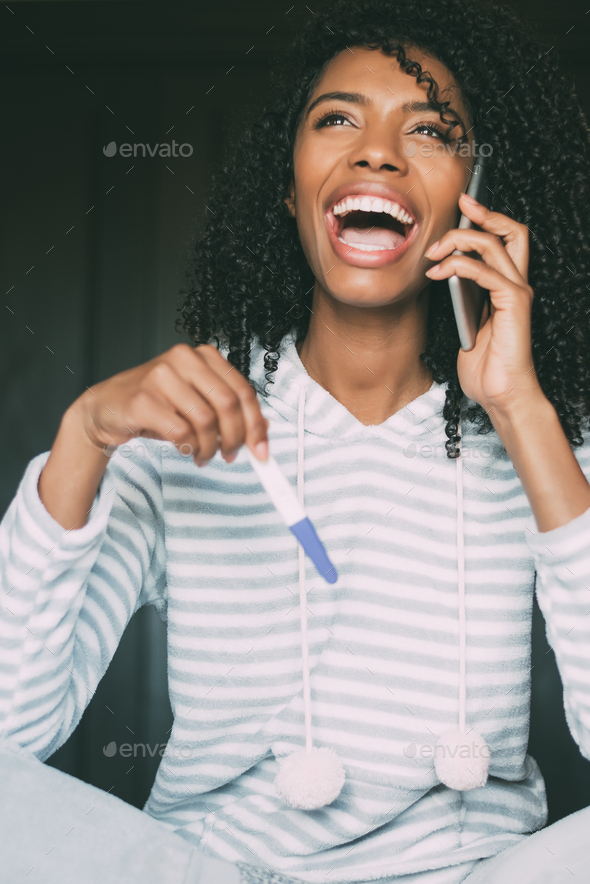 happy black woman with a pregnancy test and smartphone on bed - Stock Photo - Images