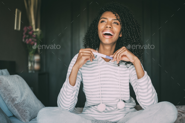 happy black woman with a pregnancy test on bed - Stock Photo - Images