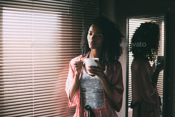 pretty black woman standing at the window with cup of coffee - Stock Photo - Images