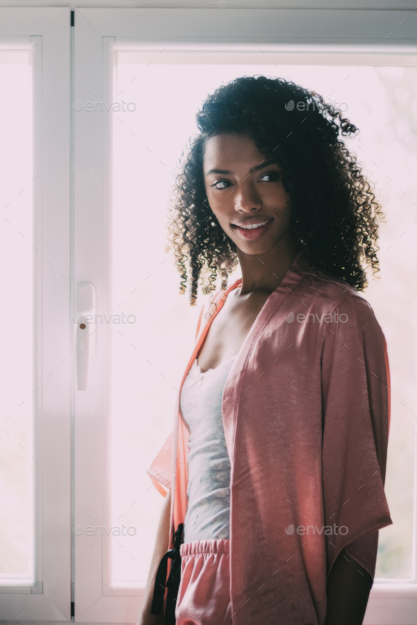 pretty black woman standing at the window - Stock Photo - Images