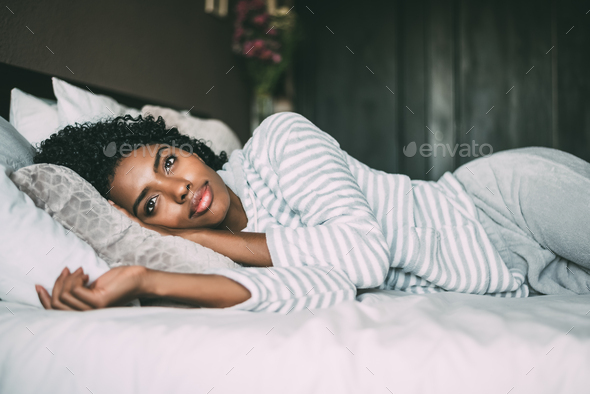 close up of a pretty black woman with curly hair smiling and lying on bed looking away - Stock Photo - Images