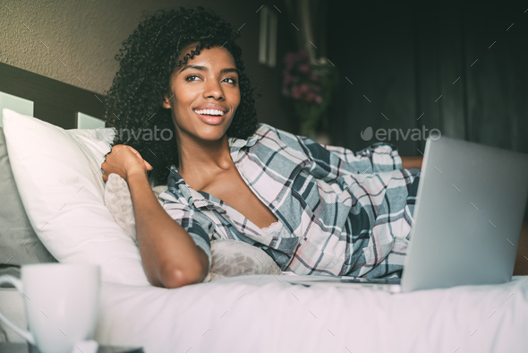 beautiful black woman on bed with laptop and cup of coffee - Stock Photo - Images