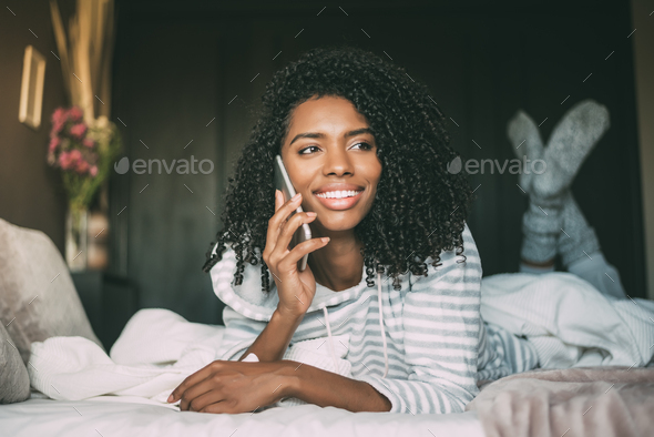 close up of a pretty black woman with curly hair smiling and using phone on bed looking away - Stock Photo - Images