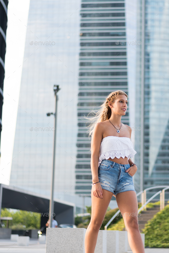 beautiful blonde woman wearing short jeans walking on the street - Stock Photo - Images
