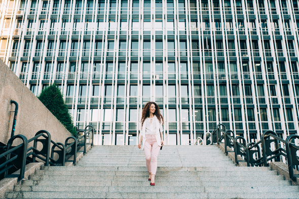 Young redhead business woman walking on the stairs - Stock Photo - Images
