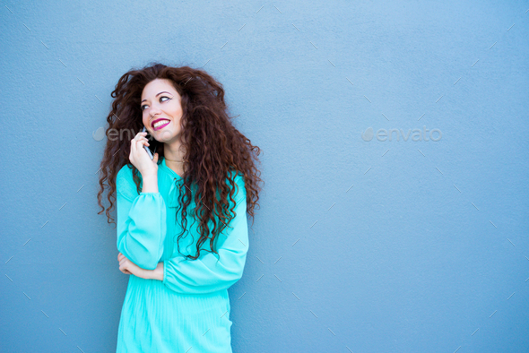 Happy young woman on the mobile phone by a colorful wall - Stock Photo - Images
