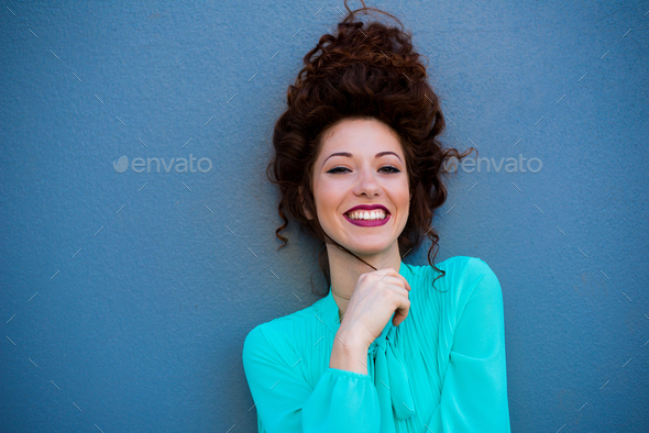 Portrait of a happy beautiful young redhead woman by a colorful - Stock Photo - Images
