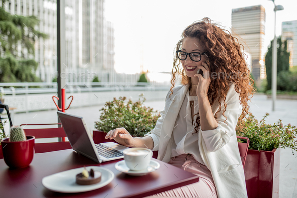 Young business redhead woman on the computer and mobile phone - Stock Photo - Images