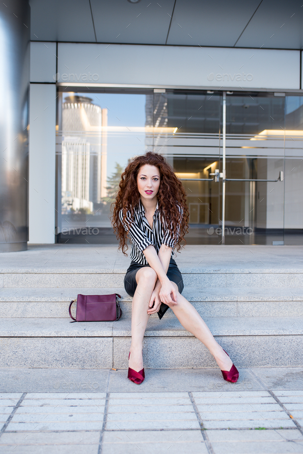 Young redhead business woman sitting on the stairs - Stock Photo - Images