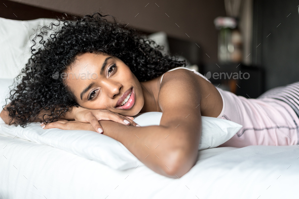 black woman happy on bed smiling and stretching looking at camer - Stock Photo - Images