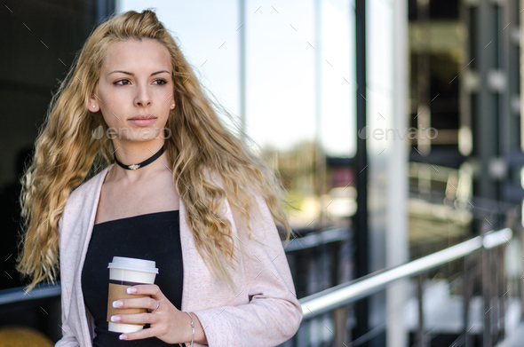 blonde student businesswoman with coffee on the street - Stock Photo - Images