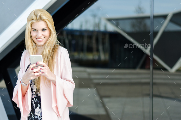 happy blonde young woman outdoor using her mobile phone - Stock Photo - Images