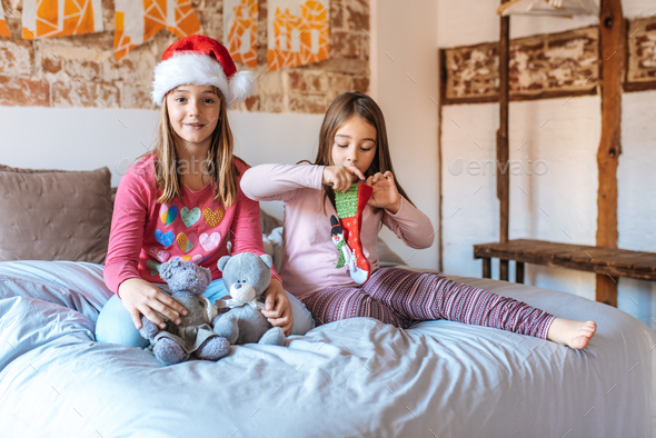 Two little sisters playing with each other in bed at home opening christmas present - Stock Photo - Images