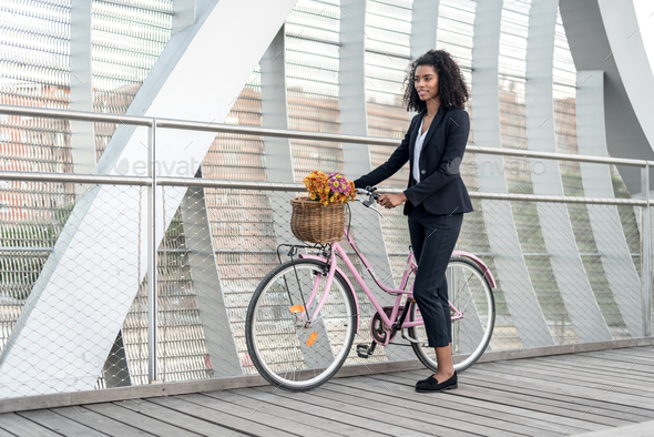 Business black woman with vintage bicycle in a bridge - Stock Photo - Images