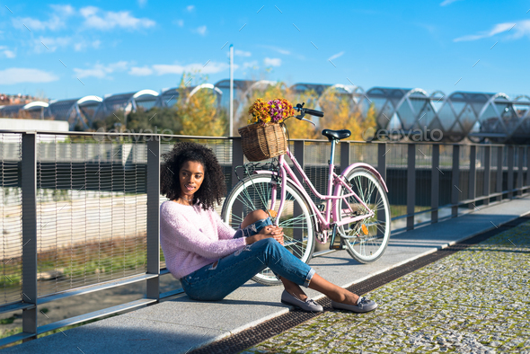 Black young woman sitting by the river with her vintage bicycle - Stock Photo - Images