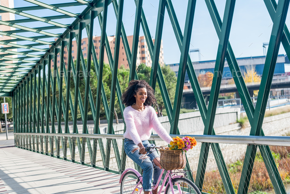 Black young woman riding a vintage bicycle - Stock Photo - Images