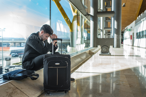 young businessman angry at the airport waiting his delayed flight with luggage - Stock Photo - Images