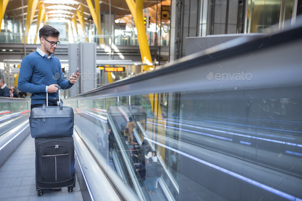 young man on the scalator at the airport using his mobile phone with his luggage smiling - Stock Photo - Images