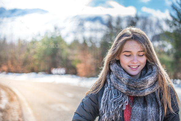 portrait Young pretty woman on a road with snow in winter - Stock Photo - Images