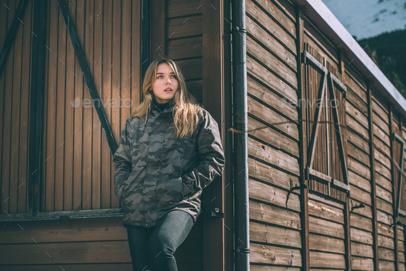 portrait Young pretty woman in winter in the snow in a log cabin wooden - Stock Photo - Images