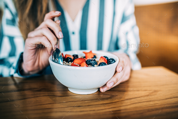 Crop woman close up eating oat and fruits bowl for breakfast - Stock Photo - Images