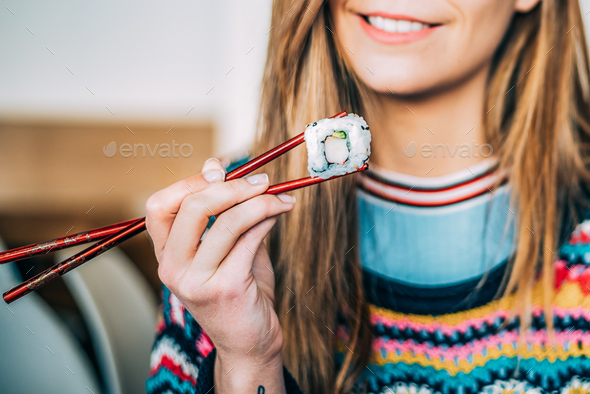 Crop woman eating sushi - Stock Photo - Images