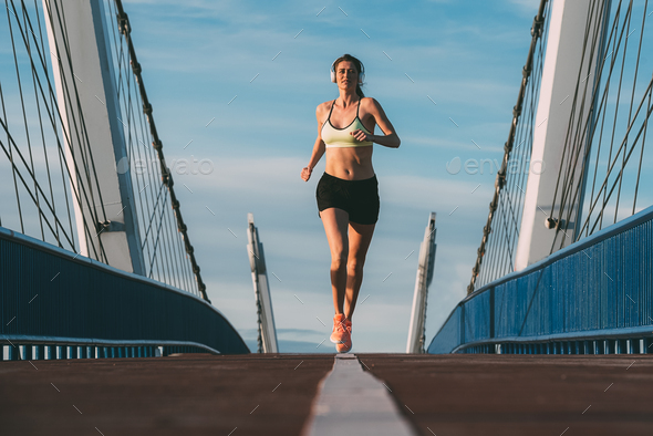Young fit blonde woman running on the bridge - Stock Photo - Images