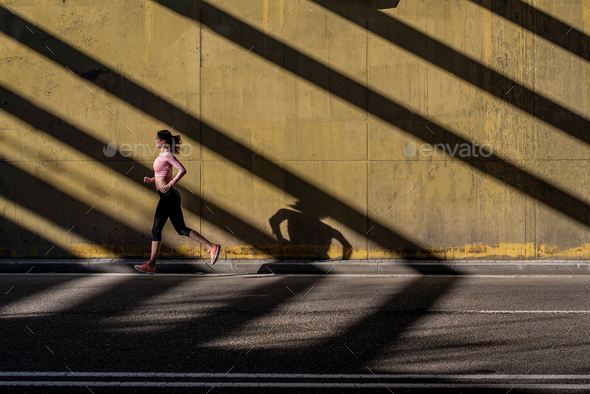 Young fit blonde woman running in the street - Stock Photo - Images