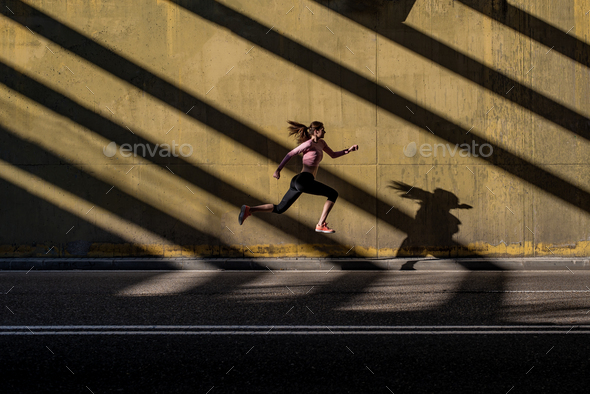 Young fit blonde woman jumping in the street - Stock Photo - Images