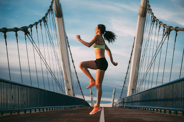 Young fit blonde woman jumping on the bridge - Stock Photo - Images